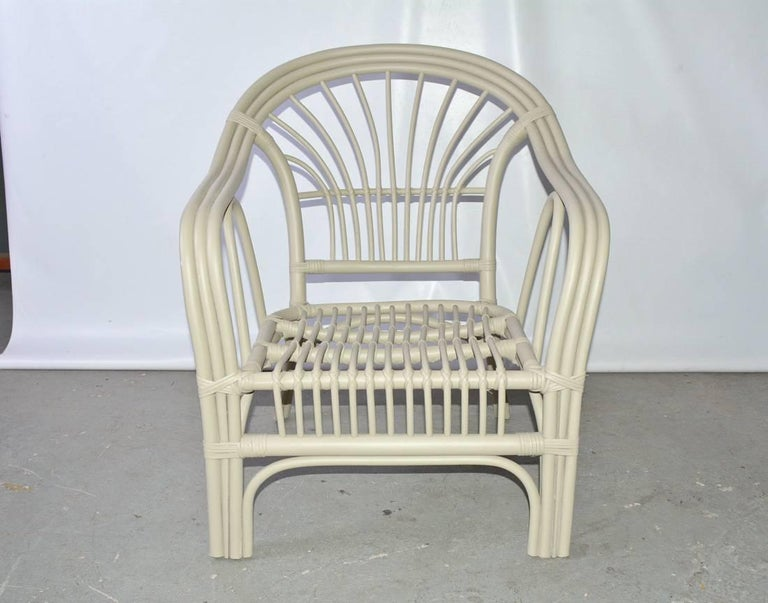 The vintage porch armchair is made of bent rattan bound by strips of rattan. 