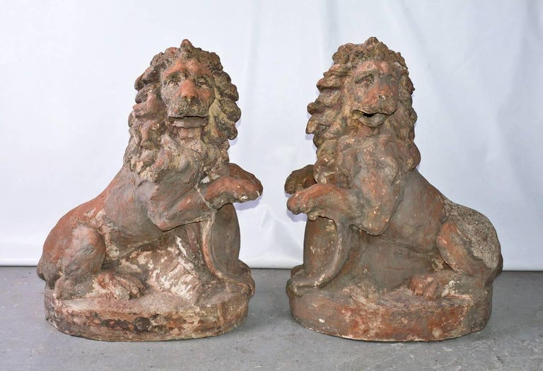 Impressive pair of 19th century Baroque style terracotta lions, with animated expressions, fully-maned heads turned in opposing directions.