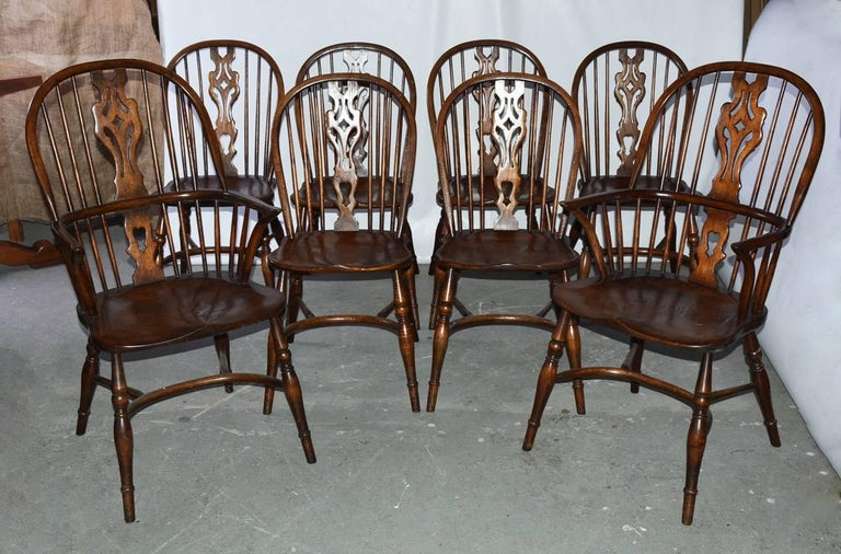 Set of eight Georgian style windsor dining chairs. Handcrafted, wonderful patina. The set is not identical. There are some difference in size and the size of pierced splat decoration on chair backs. Please see photos to see differences. Set includes