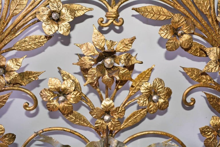 The elaborate Italian gilt metal floral wall decoration has spikes located up the sides and at the top and bottom for holding 14 candles. The whole composition is held in place with a silver gilt, rippling metal bow. The centers of the flowers are