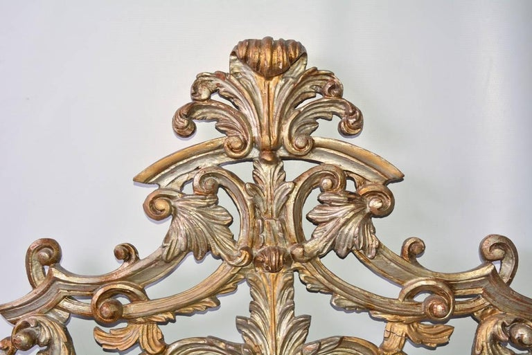 The antique hand-carved wood ornament is painted in silver gilt. The decorative elements are attached to a horizontal board at the bottom that has rectangular slots underneath, two in the middle and one at each end. In the back is a vertical flat