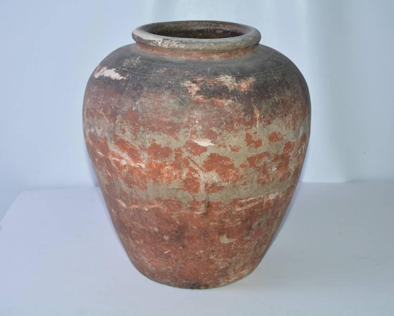A very fine quality late 19th century medium size terracotta urn or jar with gorgeous original patina. This terracotta storage jar or jardiniere features a lip leading to gracefully shaped rounded belly. The planter is nicely weathered in a red