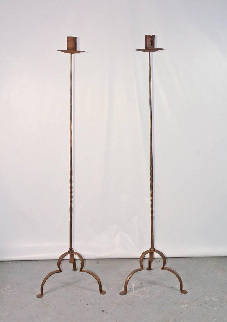 Pair of Baroque wrought iron floor standing torchers or candleholders having a slender shaft and gilt finish supported on three shaped downs wept legs ending in penny feet.