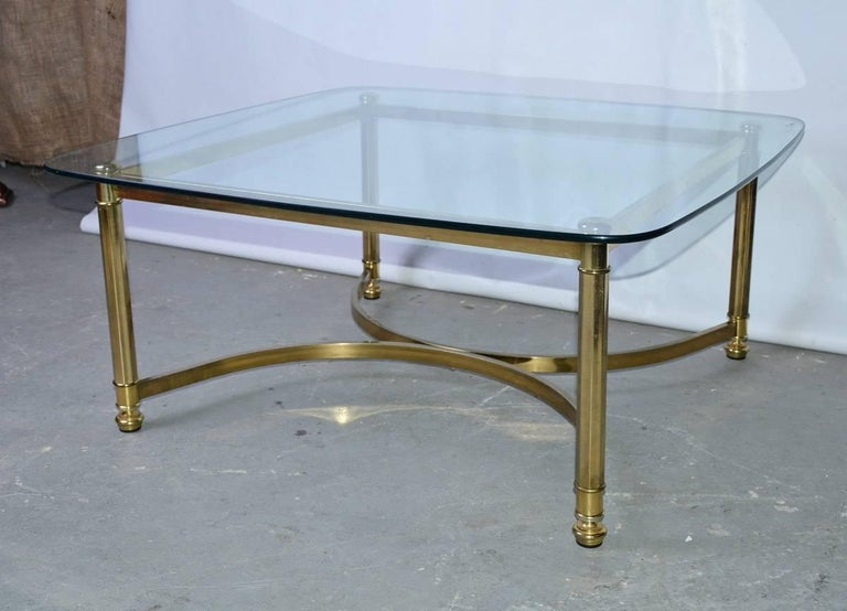 Neoclassical style Italian coffee table with brass base and glass top.