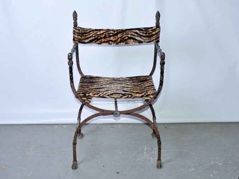 A 19th century Italian Curule Savonarola chair, handmade wrought iron, bronze paw feet, and decorative finial.