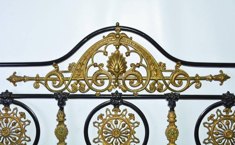 Napoleon III style queen headboard is constructed of iron and bronze painted black with elaborate solid brass detailing, including filigree rosettes and pediments. The outer posts and legs have a scattering of hand-painted pansies and leaves.