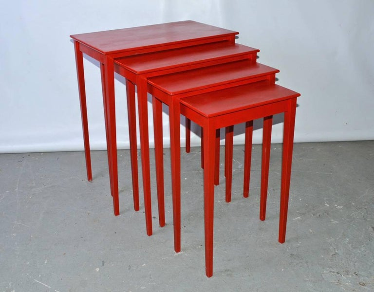 The vintage four-piece nesting tables slide underneath each other, have tapered legs and are painted in Chinese red lacquer.  Second table - D 15