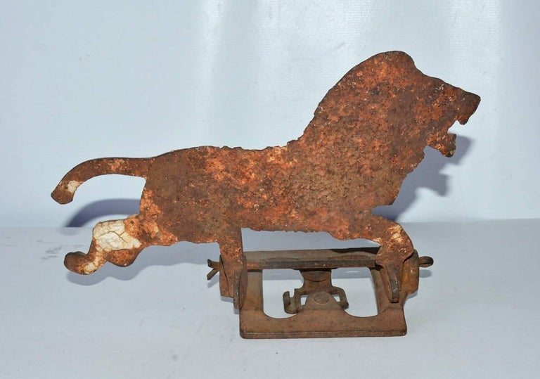 Rare antique cast iron shooting gallery target in the shape of a lion still attach to the base that supports the lion when a shooter knocks it over.  Wonderfully charming!  Great to display as a sculpture.