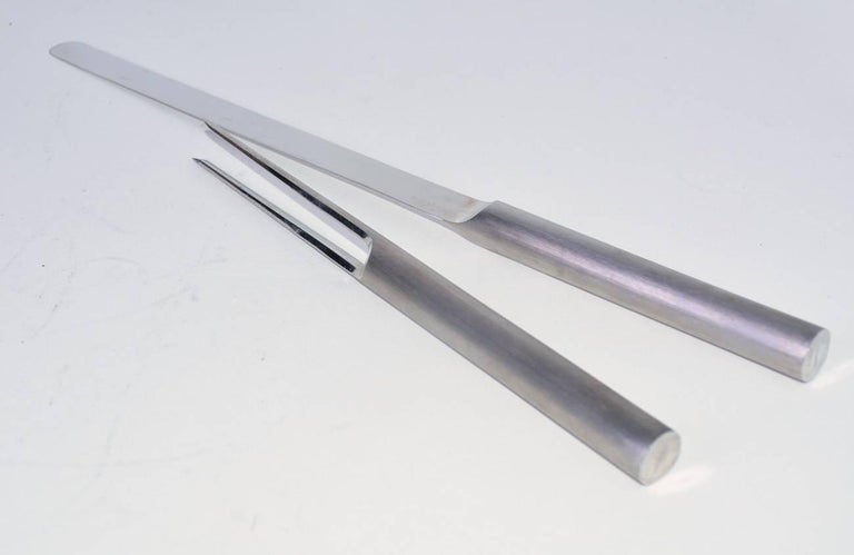 A beautifully designed fork and knife carving set crafted from stainless steel by Cini & Nils, OPI Milano in original boxes. Measure: Second piece: D 0.75