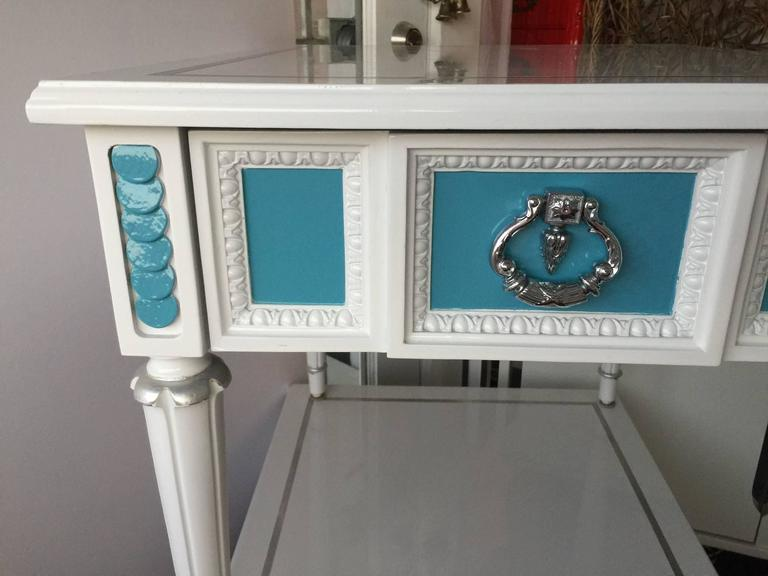 Hollywood Regency style white and blue lacquered side tables/nightstands. One-drawer with an original heavy handle that has been chromed. The table top has been detailed with a silver leaves inlay. Finished in the back, the side tables/night tables