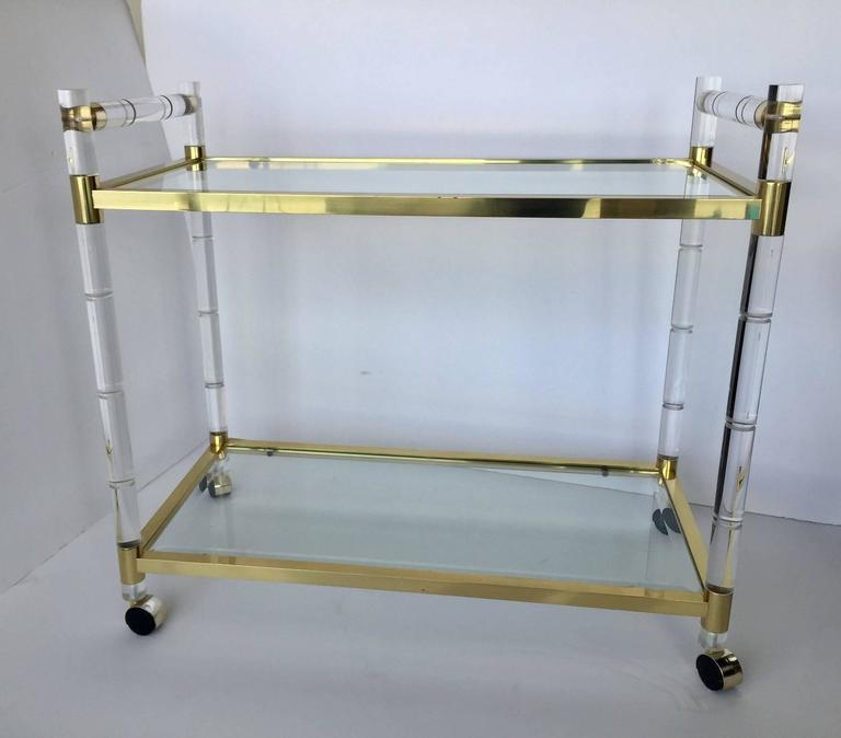 Elegant Lucite and brass bar-cart designed and manufactured very close to the style of Charles Hollis Jones. 