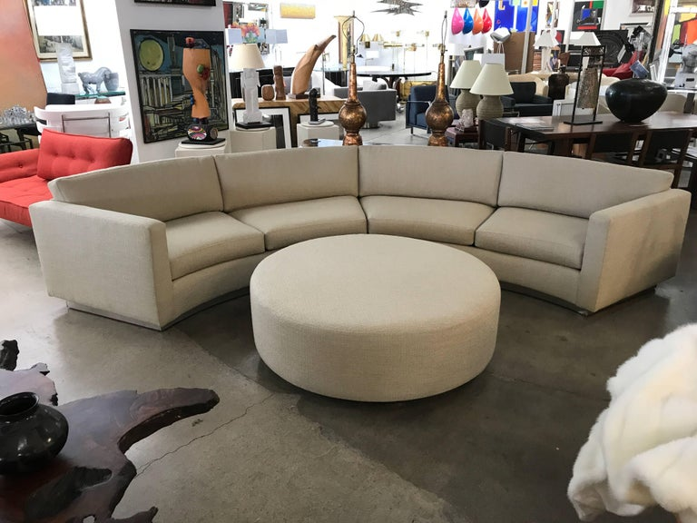 A great looking Thayer Coggin by Milo Baughman designed sectional curved sofa with matching ottoman. We have had the sofa and ottoman completely restored and re-upholstered. Additionally we have added a plinth base covered in brushed steel. This