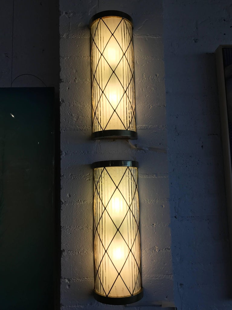 A beautiful pair of wall-mounted brass and glass sconces. Nice Hollywood Regency styling. We believe these sconces are American but the glass appears handblown Italian, likely Murano. They are quite lovely when lit. The switches have two settings,