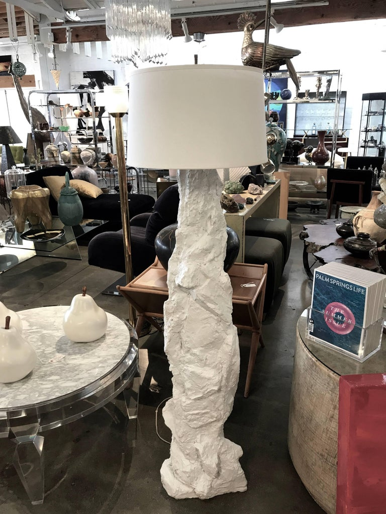 A nice tall plaster lamp in the manner of Sirmos, like a rock formation. It bears a monogram J.m.h. It also bears a copyright that seems to read 96 usc. New hardware on top original cord. Due to the nature of the rock like structure it's difficult