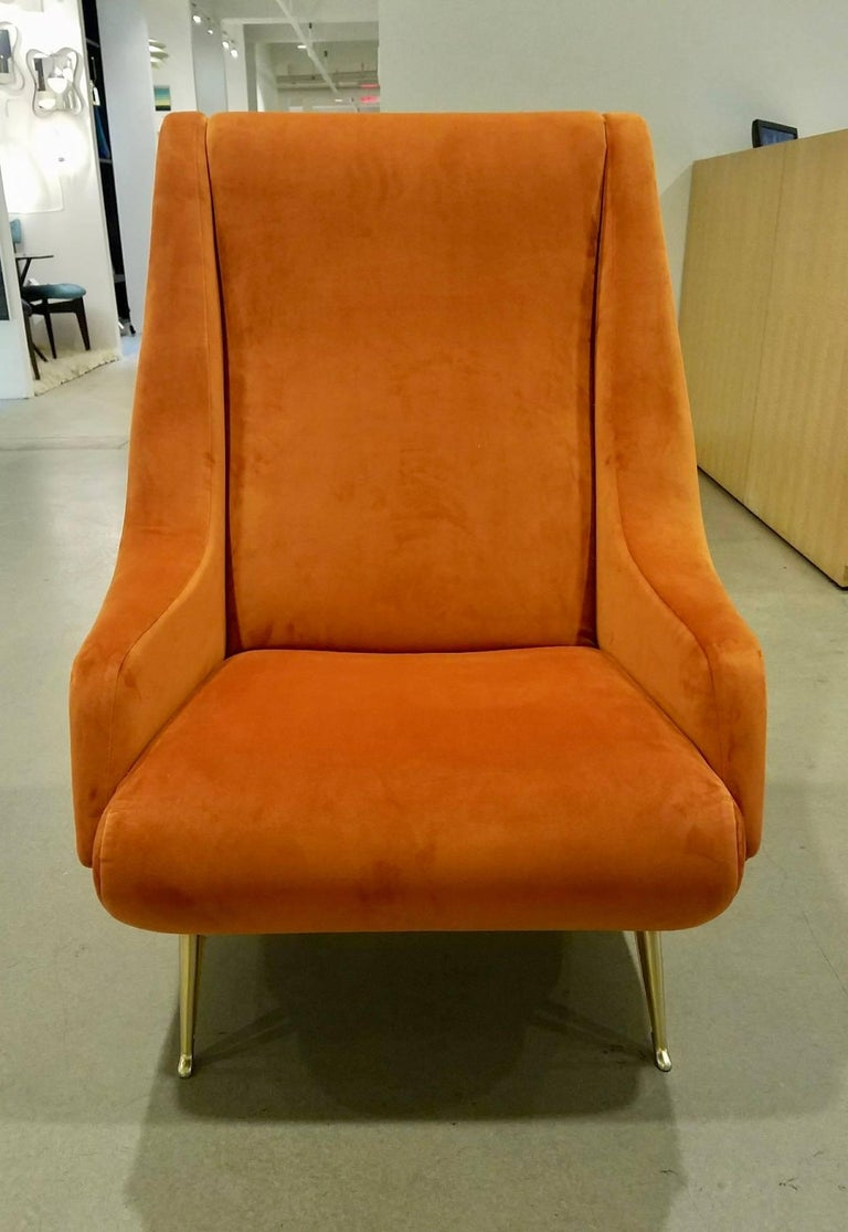 A pair of midcentury Italian newly upholstered burnt orange ultra suede armchairs attributed to ISA with generously proportioned, slanted high backs, and sinuous shaped arms around tightly upholstered seats, resting on gold-toned, splayed and