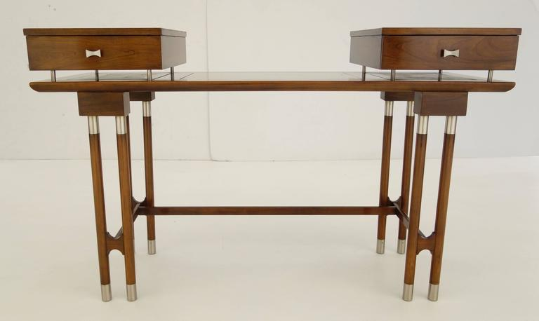 A Mid-Century writing desk or vanity, the top featuring two pull-out drawers floating on the flat surface comprised of three inset lighter wood panels resting on eight tubular legs capped at both ends with nickel hardware connected by two short and