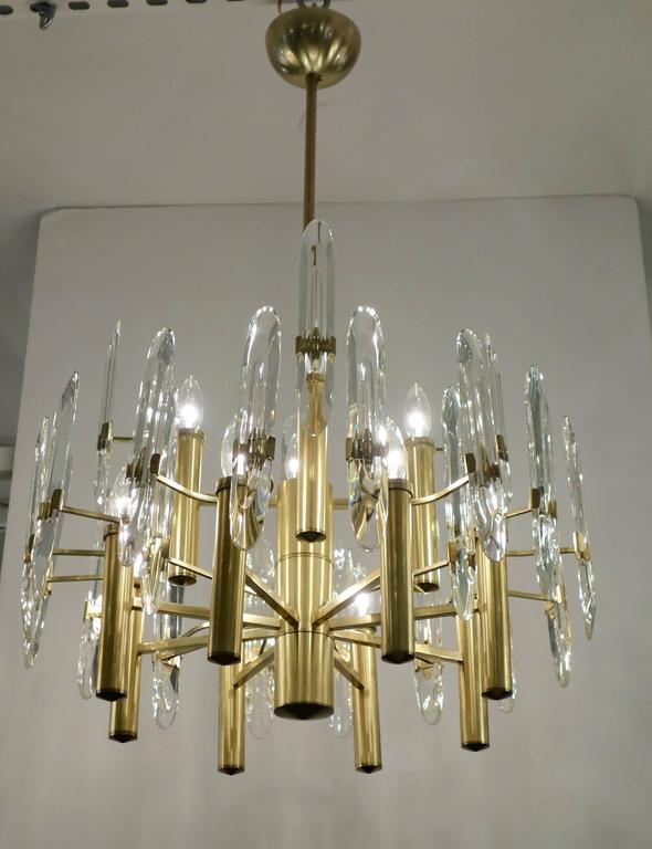 Italian Mid-Century Sciolari chandelier featuring 12 sockets and 24 beveled glass prisms radiating from a central cylinder from multi-levels secured with both double and single arm brackets from the re-plated satin brass frame, rewired for the