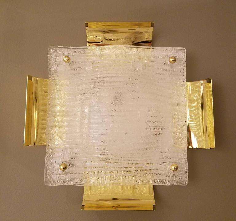 "A large pair of 14"" Austrian Mid-Century sconces by Kalmar comprised of handblown square ribbed glass panels with rectangular concave brass sheets extending from each side from a white matte back plate held together with four brass screws, with"