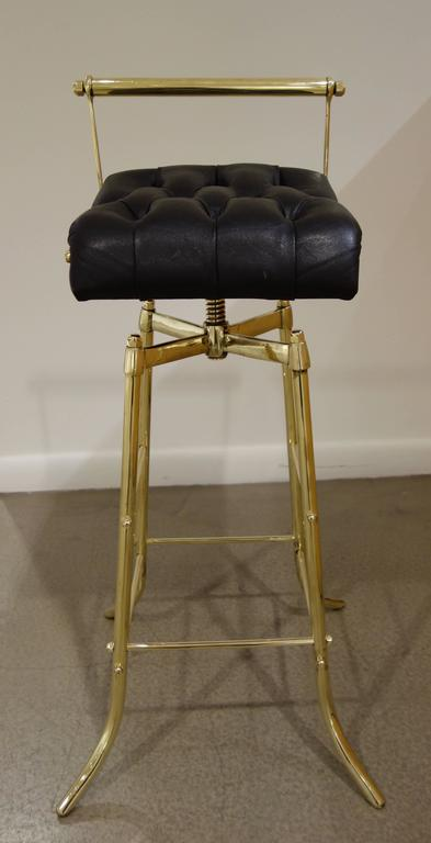 A set of three circa 1970s Italian brass bar stools with original, tufted black leather upholstery, the revolving seats resting on professionally polished, adjustable brass bases.