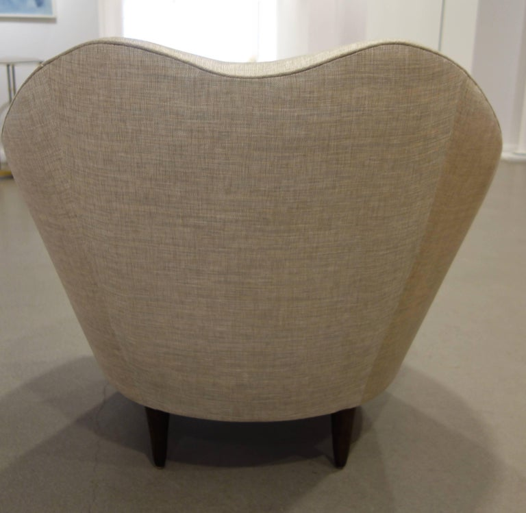 A pair of curvilinear pair of Italian lounge chairs, by Federico Munari, the tops with sinuous dips with broad curved backs and firm loose, deep cushions resting on four dark brown conical, tapered wood legs newly upholstered in woven bronze and