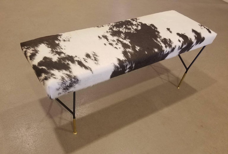 An Italian midcentury style bench, the top newly upholstered in a crème and dark brown-black new cowhide, resting on black metal legs each attached at two points from the underside of the seat forming a triangle, ending in a single, elongated brass