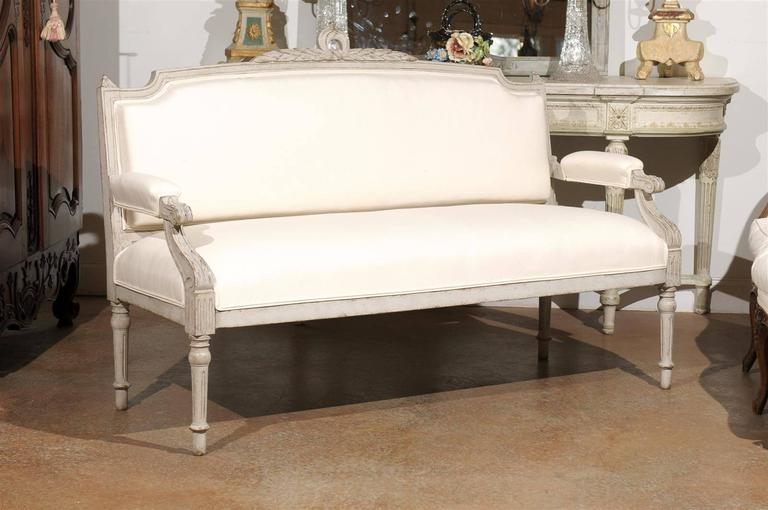 A Swedish painted wood Neoclassical style sofa from the late 19th century with original paint, carved crest and new upholstery. This Swedish painted sofa features a slightly slanted back, adorned with a delicate foliage motif on the crest, flanked