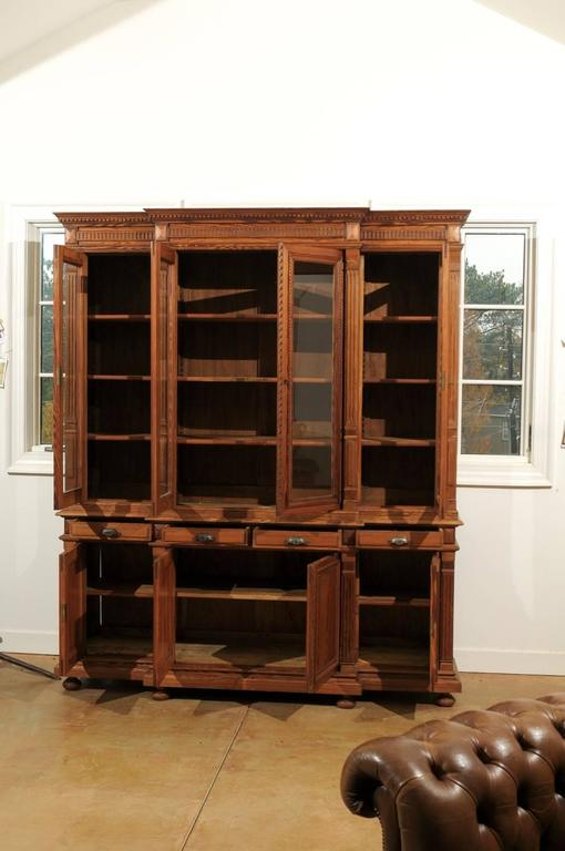 A French pitch pine and glass door breakfront bookcase from the turn of the century. This French bookcase features four glass doors making up the upper part of the piece. The bookcase is adorned with a dentil molding on the upper cornice,