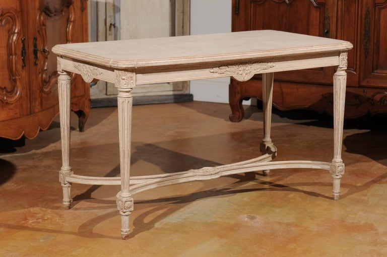 A Swedish Gustavian style painted wood coffee table with fluted legs and cross stretcher from the early 20th century. This Swedish coffee table features a rectangular top with beveled edges and rounded corners, sitting above an exquisitely carved