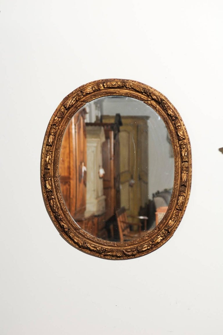A French Louis XIV period carved oval mirror with giltwood frame from the early 18th century. This French oval mirror features a new mirror plate set within a molded frame, adorned with carved rosettes on its outer border. Born in the last years of