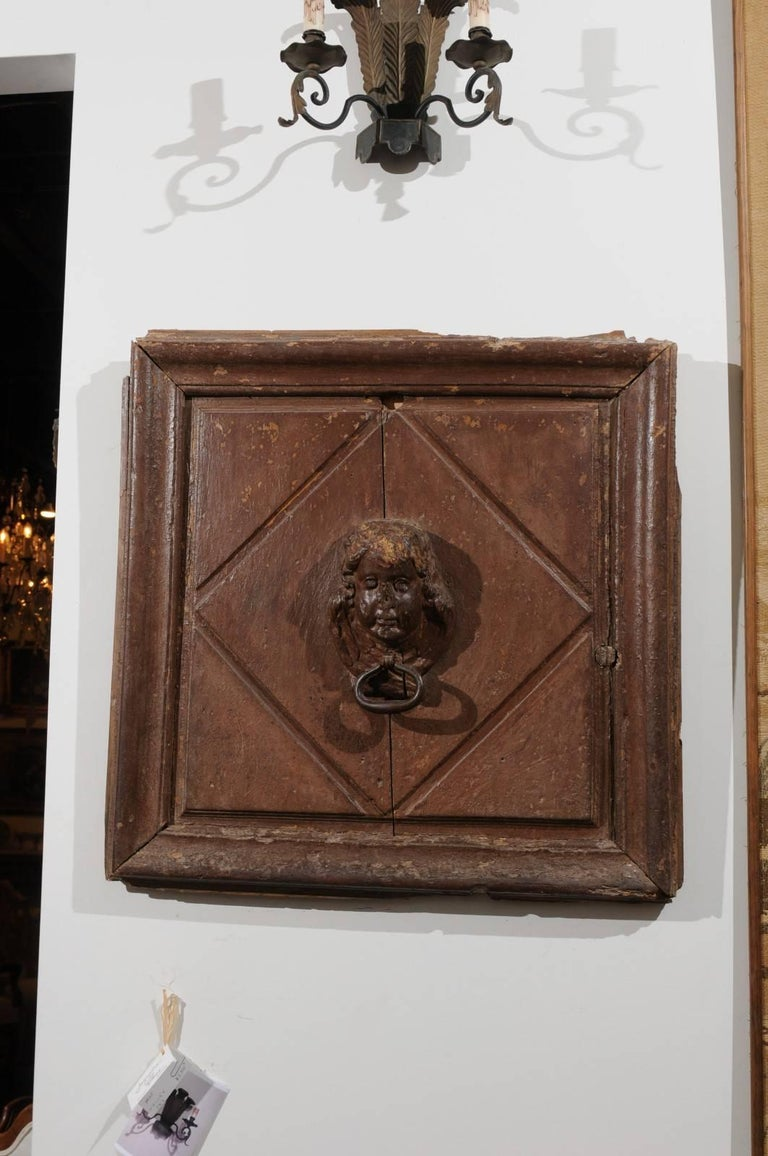 A pair of French 17th century square wooden wall fragments with high relief cherub carvings. Each of this pair of architectural pieces features a cherub face carved in high relief, surrounded by a diamond motif. The grand simplicity of the lines is