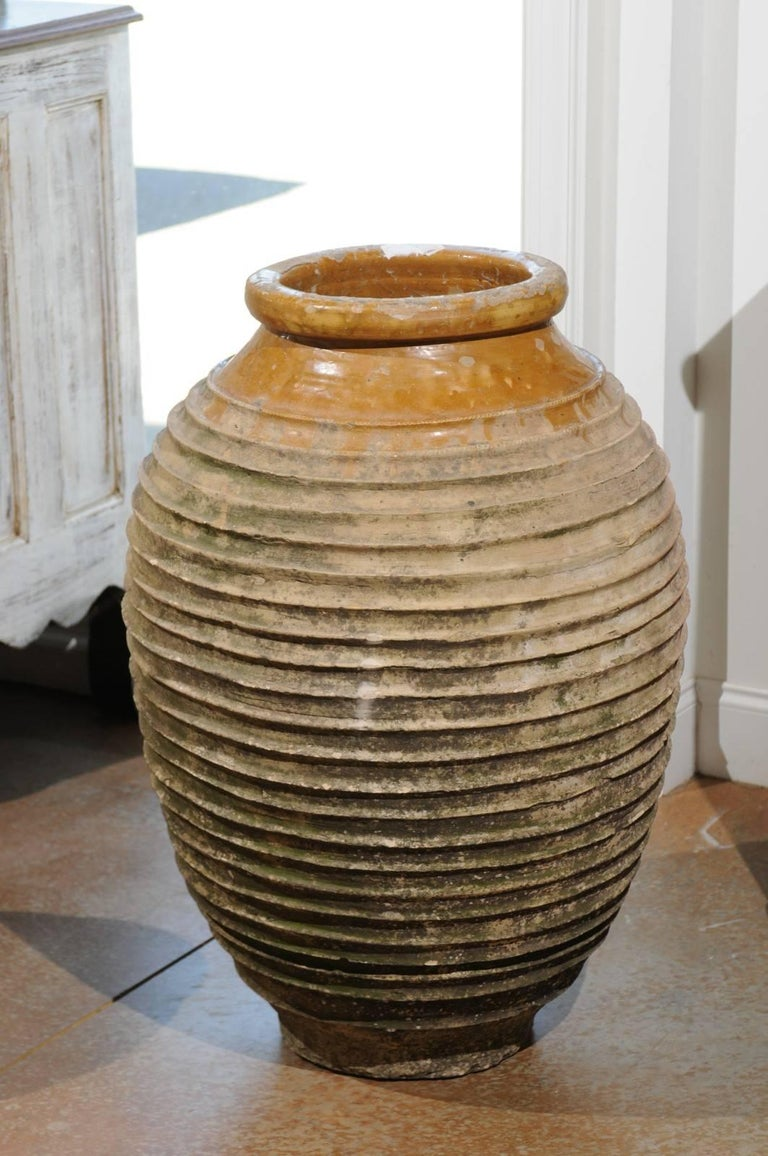 An early 19th century Greek medium size terracotta ribbed olive jar with traces of glaze in the upper section. This olive terracotta jar was born in Greece in the early 1800, where it was used to store olive oil. It features a typically Greek style