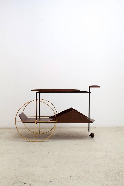 A Brazilian Modernist Classic, the 'JZ' was designed in the 1950s by Jorge Zalszupin. Its pair of slender but oversized brass wheels dramatically play off the triangle-sided bottom shelf; the tray on top is removable. Available in Honey Imbuia wood.