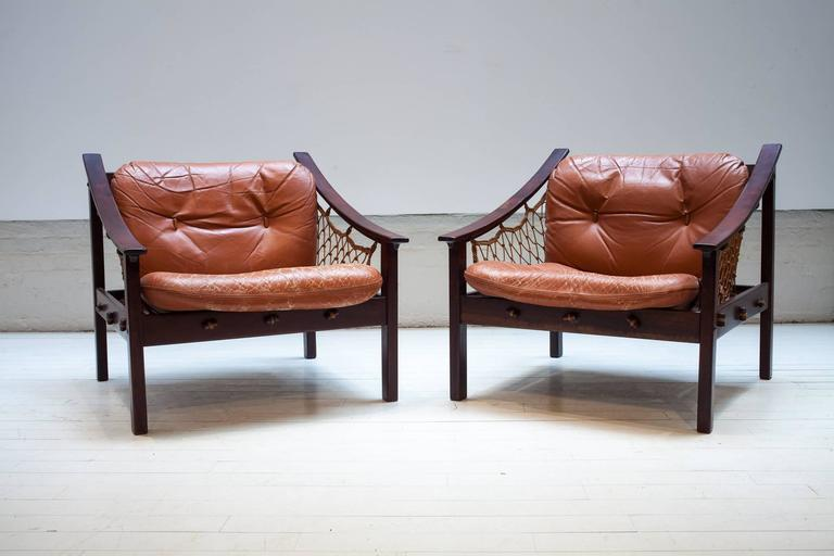 The Amazonas armchair designed by Jean Gillon riffs on the aesthetics and techniques of Brazilian fishermen's boats and nets for their structures and materials. Circa 1960's. Sold as a set of two.