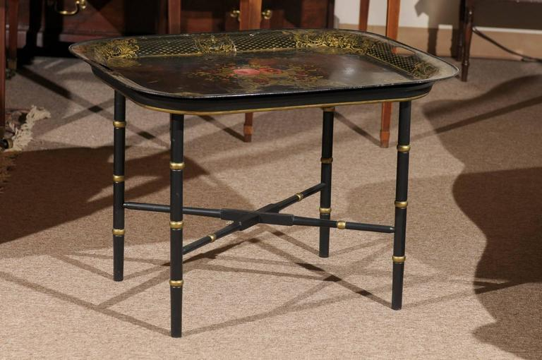 A French tole tray with center painted flower basket design and gilt foliage detail on boarder. The tray on later wood stand with gilt detail and X-form stretcher.