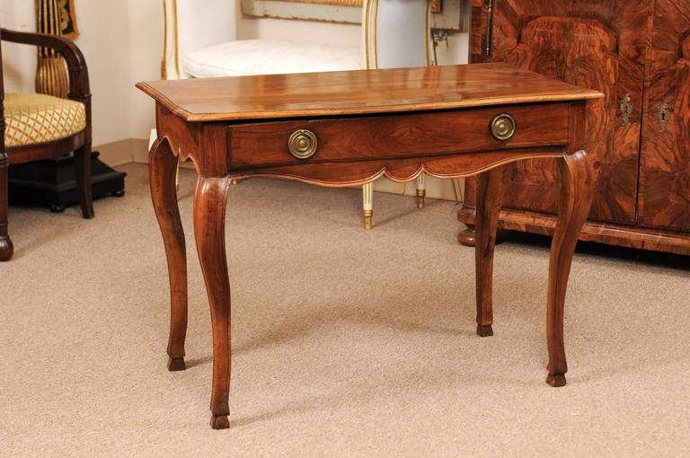 An 18th century Louis XV period walnut table with long drawer, finished back and cabriole legs terminating in graceful hoof feet, France, circa 1760.