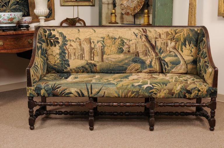 French Louis XIII style oak canape with 18th century Aubusson tapestry, wing sides, turned legs and stretcher.