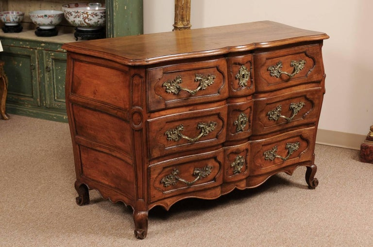 Louis XV period commode in walnut with three-drawers, linen fold front, and scroll feet, France 18th century.