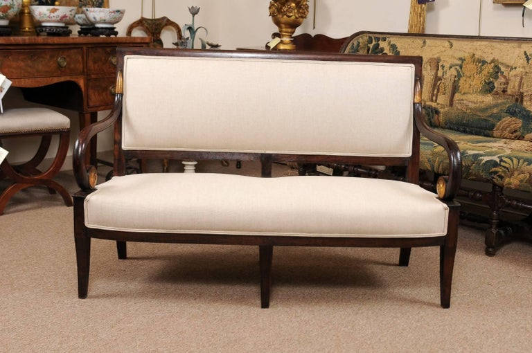 Empire Period Settee in Mahogany with Scroll Arms featuring Gilt Accents and Splay Legs, France circa 1820. The wood finish is in a dark chocolate hue juxtaposed against the light beige linen upholstery (new).