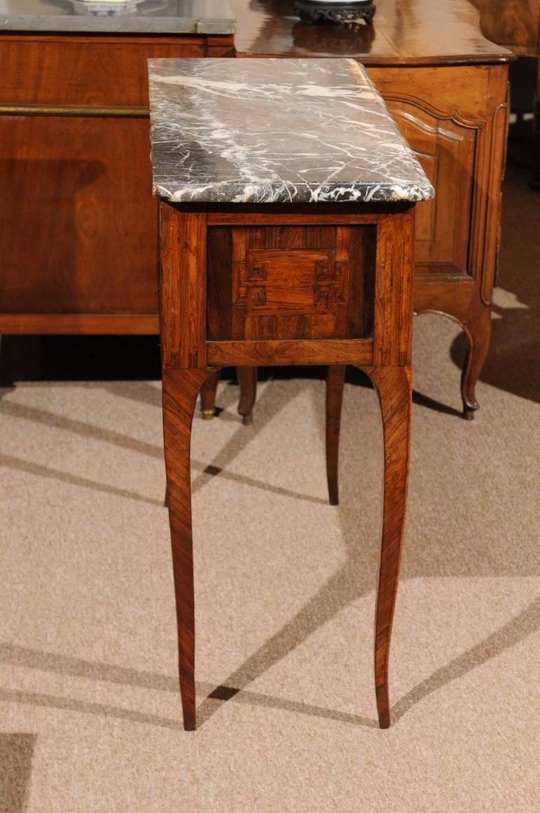 The commode en console with grey marble top resting on rectangular base in walnut and tulipwood with cross-banding and inlay to drawer and brass ring pulls. All resting on cabriole legs.