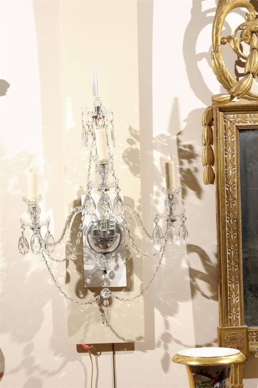 Pair of cut crystal arm sconces with three lights.