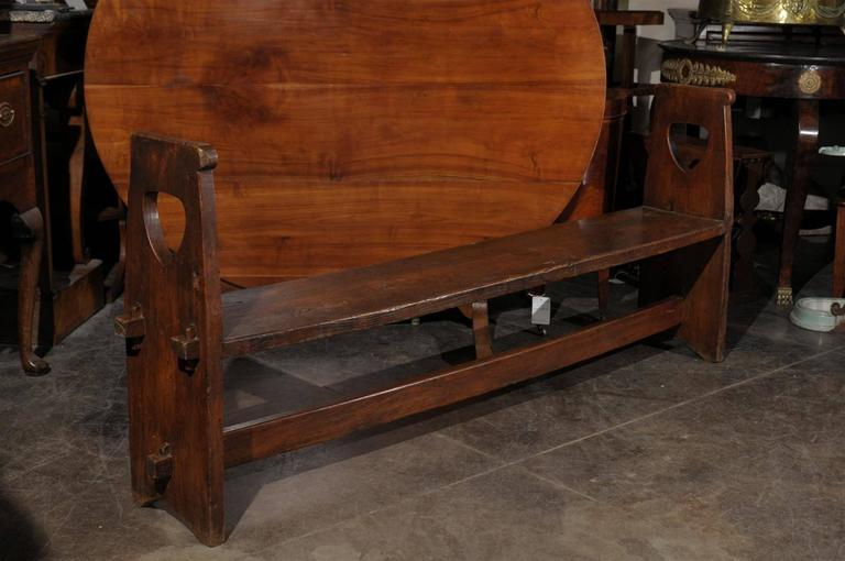 A long Italian wooden bench with stretcher and sides from the 19th century.  This narrow wooden Tuscan bench from the early 19th century features a stretcher and a rectangular seat. This seat is inserted in groves in the sides, and has knuckles that