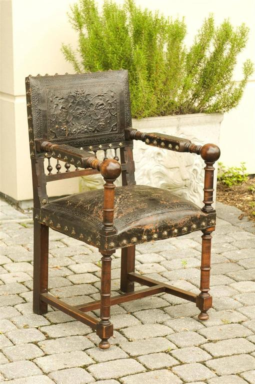 A French wooden armchair with leather upholstery from the turn of the century (19th-20th). This French wooden chair from circa 1890-1910 features an exquisite original black leather embossed back and seat, as well as partially upholstered open arms.