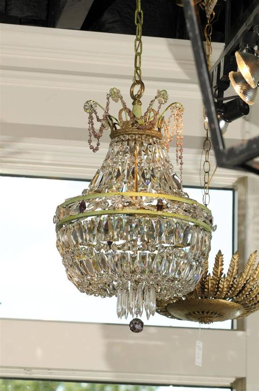 This petite French crystal chandelier from the mid 20th century features a lovely basket shape. Reminiscent of the Empire taste, the chandelier is made of a metal double ring adorned with diamond shaped crystals of amethyst color. The crystals give