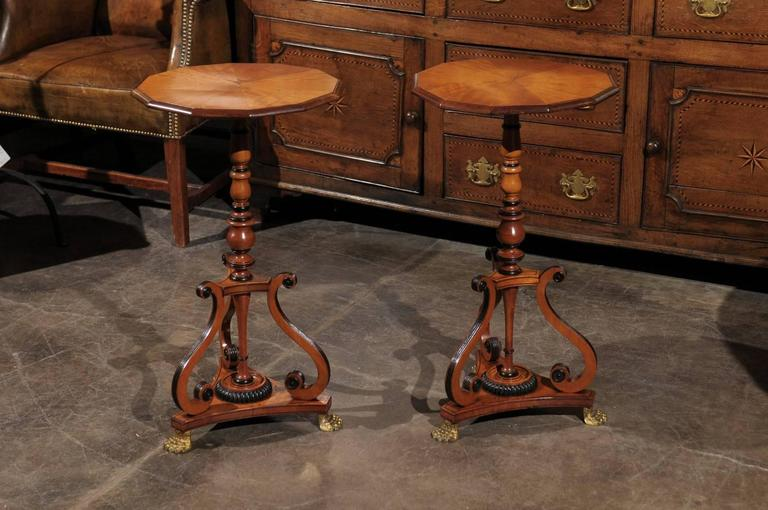 A pair of early 19th century English period Regency parcel-ebonized wooden side tables featuring a dodecagon molded top over a baluster-turned support with ebonized rings. Each table is raised on a triangular base with concave sides below three