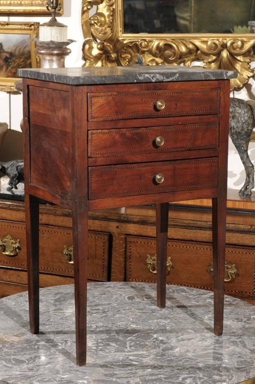 A petite French mid-19th century three-drawer commode. This French commode from circa 1830 features a rectangular grey veined marble top over three nicely hand-carved dovetailed drawers with delicate banding and round brass pulls. This delicate