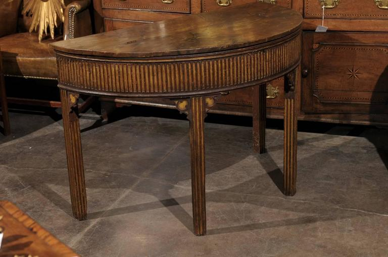 A pair of English Neoclassical style painted wood demi-lune consoles tables with marbleized lift tops, fluted aprons, and straight bracketed legs from the late 19th century. Each of this pair of English demilunes features a semi-circular top with