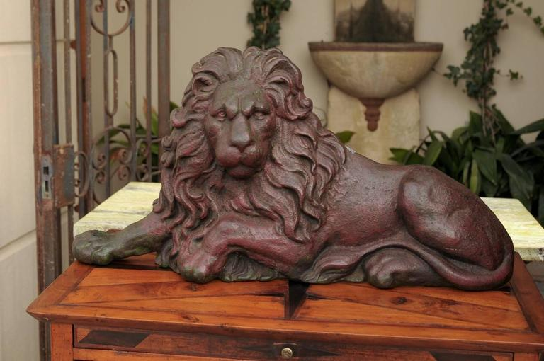 A cast iron lion doorstop from Victorian England. This 19th century Victorian cast-iron flat-back reclining lion is an elegant doorstop, probably after the magnificent original bronze pair by Sir Edwin Landseer displayed in Trafalgar Square. The