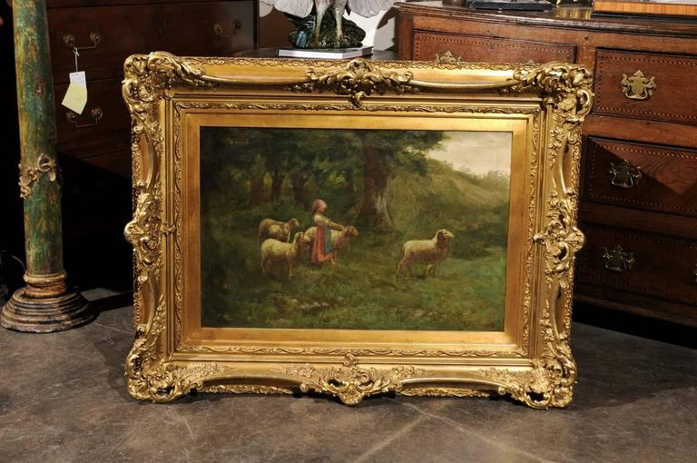 This continental large size turn of the century (19th-20th) oil painting on canvas is set in an antique giltwood frame. The scene is placed in what seems to be the edge of a forest. A lovely shepherdess, dressed in red and blue, is surrounded by