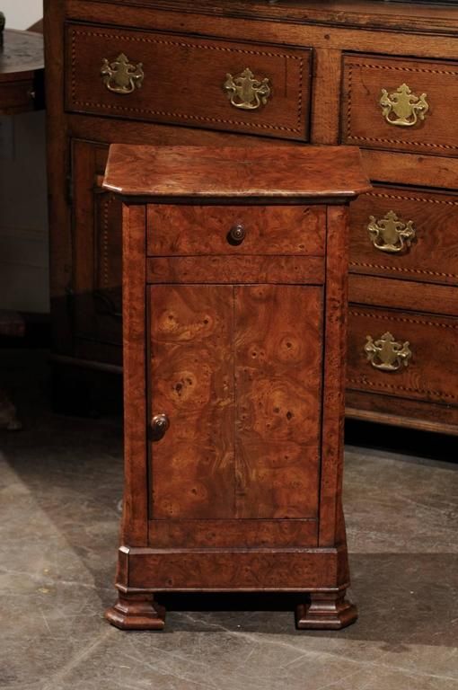 This English burl wood pot cupboard from the late 19th century features a rectangular top with chamfered front corners over a single drawer above a cabinet door, both adorned with a single wooden pull. Raised on two nicely carved front feet and
