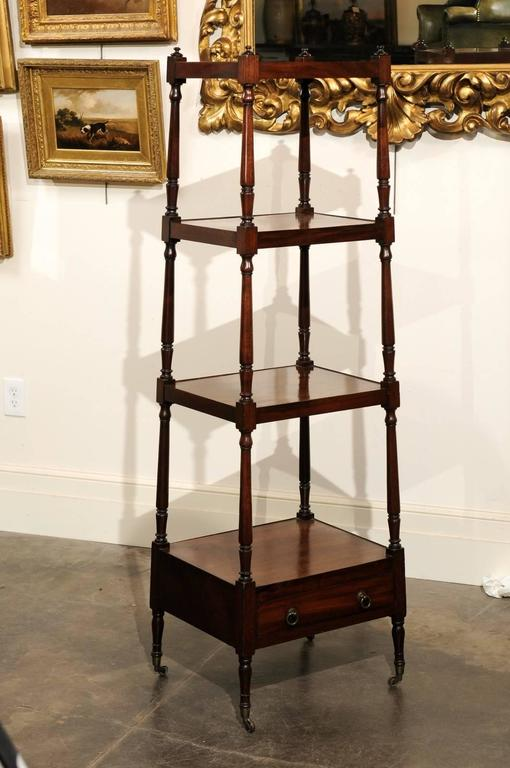 This English mid-19th century mahogany trolley features four graduated shelves over a single drawer. The shelves are secured by four turned supports on the sides, topped with discreet finials. The single drawer placed in the lower section opens with